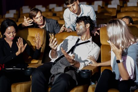 Annoying man talking on the mobile phone at the movie theater people in cinema is angry him