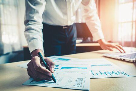 Un homme d'affaires comptable ou un expert financier analyse le graphique du rapport d'activité et le tableau des finances au siège social. Concept d'économie financière, d'activité bancaire et de recherche boursière.