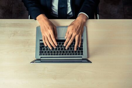 Business person or office worker using laptop computer while sitting at desk.