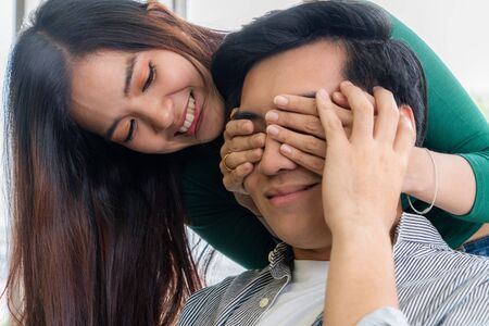 Happy Asian couple play covering eyes in living room. Reklamní fotografie