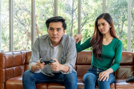 Young Asian couple suffers from computer games addiction. Family problem concept. Stock fotó
