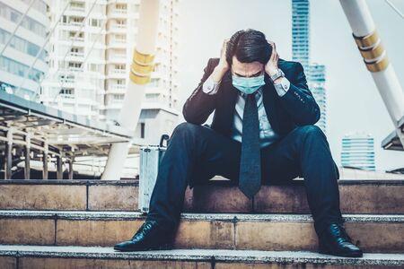 Un homme d'affaires triste et malheureux avec un masque facial protège du coronavirus ou du Covid-19. Concept de problème de chômage causé par le coronavirus Covid-19. Banque d'images