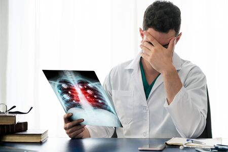 Doctor analyze Coronavirus Disease 2019 or Covid-19 displayed on x ray film. The film shows symbol of corona virus infect patient lung and respiratory organ. Medical technology and healthcare concept.