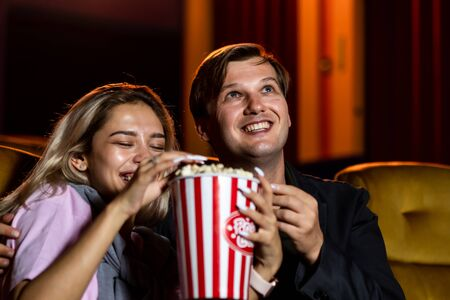 Caucasian lover enjoying to watch movie and eating popcorn together in the cinema Standard-Bild