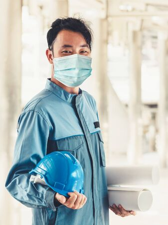 Factory worker with face mask protect from outbreak of Coronavirus Disease 2019 or COVID-19. Standard-Bild