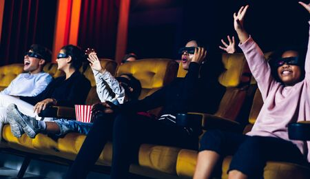 Group of people watch movie with 3D glasses in cinema theater with interest looking at the screen, exciting and eating popcorn 版權商用圖片 - 148158590