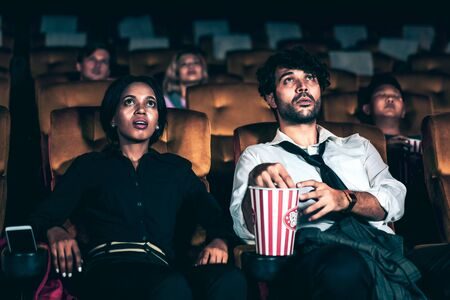 Audience sitting in a cinema and watching terrible horror. Afraid woman sitting near a man is shock and scare