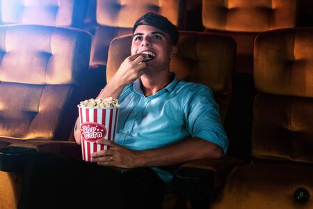 A young man smiling enjoying with his popcorn while watching a movie in theater cinema 版權商用圖片