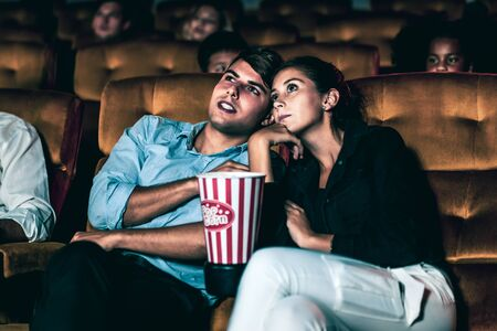 A couple of lovers watching movie shock and eyes close in the movie theater cinema.