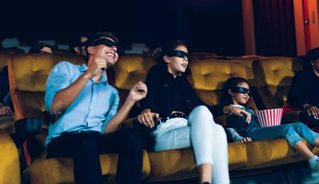 Group of people watch movie with 3D glasses in cinema theater with interest looking at the screen, exciting and eating popcorn 版權商用圖片 - 148158779