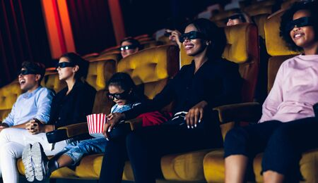 Group of people watch movie with 3D glasses in cinema theater with interest looking at the screen, exciting and eating popcorn 版權商用圖片