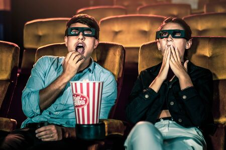 Man and woman in the cinema watching a movie with 3D glasses. with interest looking at the screen, exciting and eating popcorn 版權商用圖片 - 148158969
