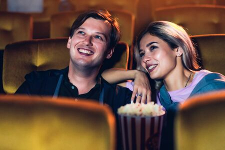 Caucasian lover enjoying to watch movie and eating popcorn together in the cinema 版權商用圖片