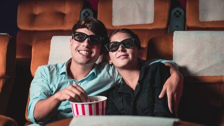 Man and woman in the cinema watching a movie with 3D glasses. with interest looking at the screen, exciting and eating popcorn