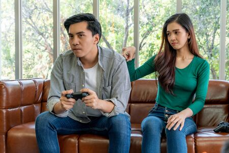 Young Asian couple suffers from computer games addiction. Family problem concept. 免版税图像