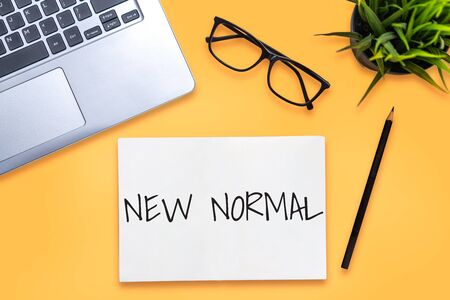 New normal concept effected by COVID 19 coronavirus that changes our lifestyle to new normal presented in word written in notebook on office desk when abnormal becomes new normal . 版權商用圖片