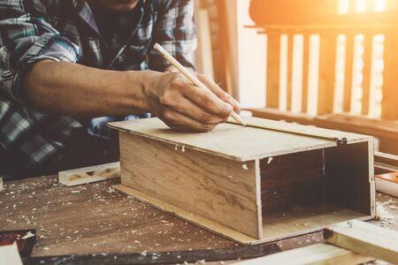 Tischler, der in der Werkstatt an Holzhandwerk arbeitet, um Baumaterial oder Holzmöbel herzustellen. Der junge asiatische Tischler verwendet professionelles Werkzeug zum Basteln. Heimwerker- und Tischlerarbeitskonzept. Standard-Bild