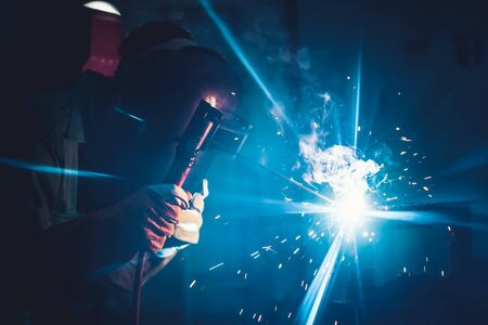 Metal welding steel works using electric arc welding machine to weld steel at factory. Metalwork manufacturing and construction maintenance service by manual skill labor concept.