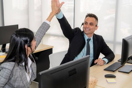 Business people wearing headset celebrate working in office . Call center, telemarketing, customer support agent provide service on telephone video conference call.