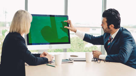 Business people in the conference room with green screen chroma key TV or computer on the office table. Diverse group of businessman and businesswoman in meeting on video conference call . Reklamní fotografie