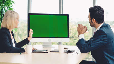 Business people in the conference room with green screen chroma key TV or computer on the office table. Diverse group of businessman and businesswoman in meeting on video conference call . Archivio Fotografico