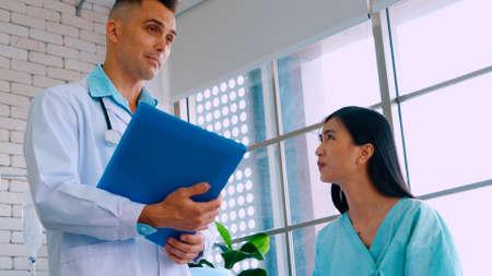Doctor in professional uniform examining patient at hospital Banco de Imagens