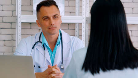Doctor in professional uniform examining patient at hospital Stock Photo