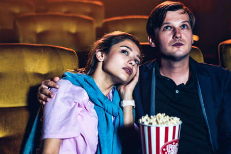 Caucasian man and woman watching a sad movie and his girlfriend crying