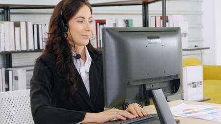 Business people wearing headset working in office to support remote customer or colleague. Call center, telemarketing, customer support agent provide service on telephone video conference call.