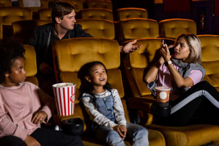 Caucasian woman talking on phone in the cinema and showing a rude gesture at the man behind her