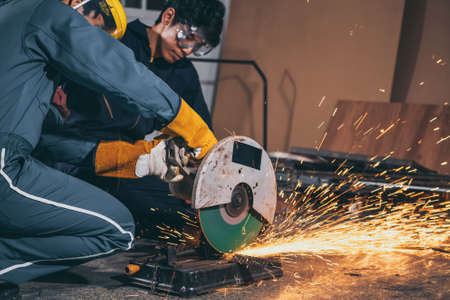 Professional mechanic man is cutting steel metal with rotating carbon blade cutter. Steel industry and workshop concept.