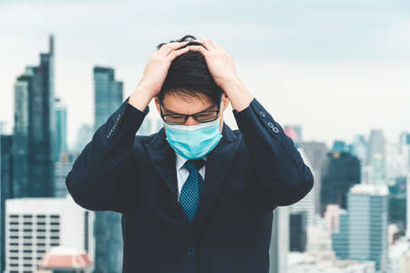 Unhappy lost business man with face mask protect from Coronavirus or Covid-19 suffers economic recession trouble. Concept of unemployment problem crisis caused by pandemic of Coronavirus Covid-19.