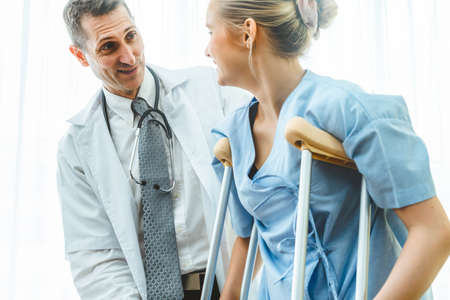 Doctor takes care of patient in crutch at hospital. Physical therapist and leg injury recovery concept.