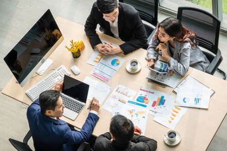 Business people group meeting shot from top view in office . Profession businesswomen, businessmen and office workers working in team conference with project planning document on meeting table .