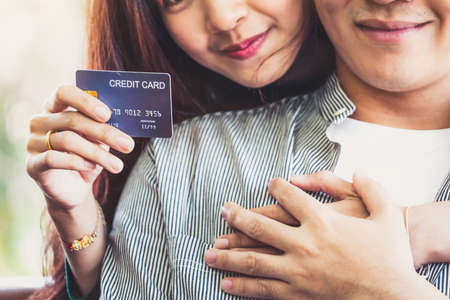 Young couple use credit card for online shopping on internet website at home. Number on the credit card is mock up. No personal information shown on the credit card. Online business shopping concept. Banco de Imagens
