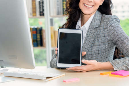 Empty tablet computer screen shown by woman in office for product , website and mobile app presentation.
