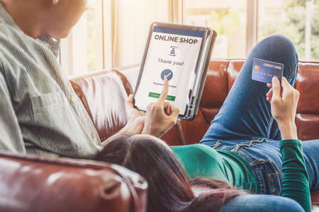 Young couple use credit card for online shopping on internet website at home. Number on the credit card is mock up. No personal information shown on the credit card. Online business shopping concept. Reklamní fotografie