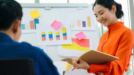 Young woman explains business data on white board in casual office room . The confident Asian businesswoman reports information progress of a business project to partner to determine market strategy . Stock fotó