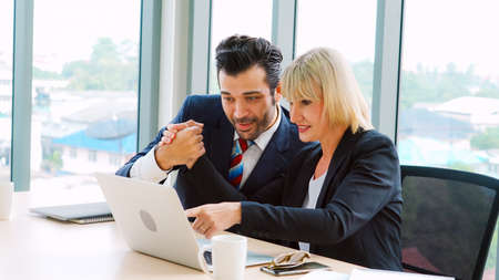 Two happy business people celebrate at office meeting room. Successful businessman congratulate project success with colleague at modern workplace while having conversation on financial data report. Stock fotó