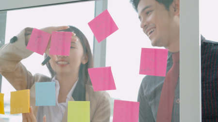 Business people work on project planning board in office and having conversation with coworker friend to analyze project development . They use sticky notes posted on glass wall to make it organized . Stock fotó