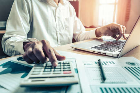 Businessman accountant or financial expert analyze business report graph and finance chart at corporate office. Concept of finance economy, banking business and stock market research. Stockfoto