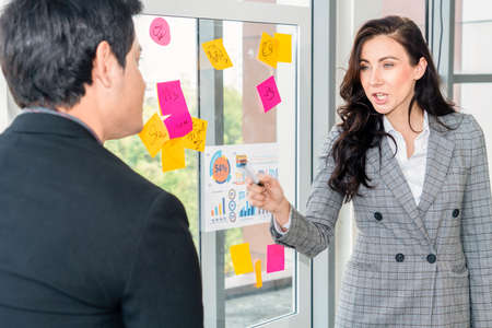 Business people work on project planning board in office and having conversation with coworker friend to analyze project development . They use sticky notes posted on glass wall to make it organized . 写真素材