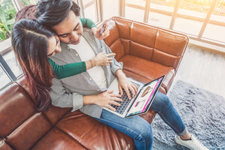 Young couple use credit card for online shopping on internet website at home. Number on the credit card is mock up. No personal information shown on the credit card. Online business shopping concept. 免版税图像