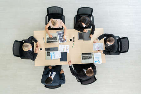 Business people group meeting shot from top view in office . Profession businesswomen, businessmen and office workers working in team conference with project planning document on meeting table . Imagens