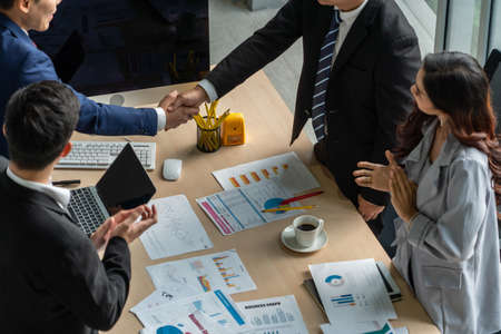 Group business people handshake at meeting table in office together with confident shot from top view . Young businessman and businesswoman workers express agreement of investment deal.