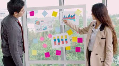 Business people work on project planning board in office and having conversation with coworker friend to analyze project development . They use sticky notes posted on glass wall to make it organized . Foto de archivo