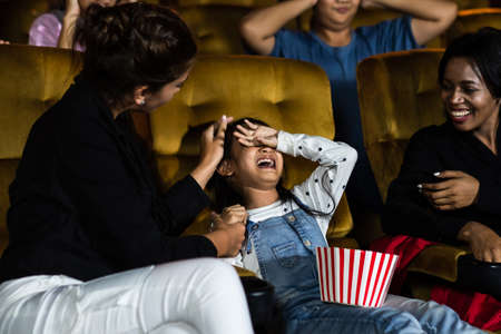 The girls cried loudly in the cinema, causing annoyance to the people sitting next to and behind them. 免版税图像