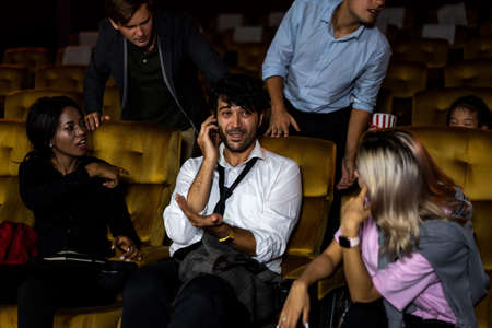 Annoying man talking on the mobile phone at the movie theater people in cinema is angry him Stok Fotoğraf