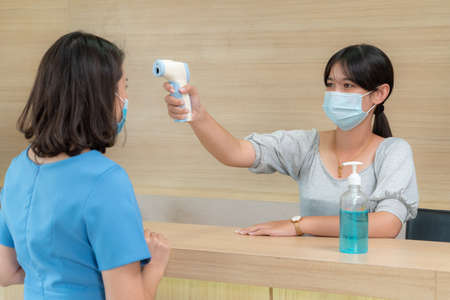 Receptionist and guest wearing face mask at front desk while having conversation in office or hospital . Covid 19 and coronavirus infection protection and protective policy concept .