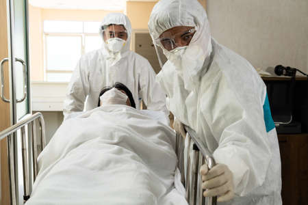 Emergency medic and doctor moving patient to emergency room in hospital . Doctor wears protective suit and face mask in concept of coronavirus and covid 19 protection and quarantine .